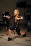 La fille blonde de forme physique de SME s'exercent pour les mains et le dos avec l'expa Images stock