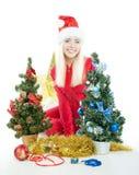 La fille blonde de Santa s'assied entre deux sapins Photographie stock