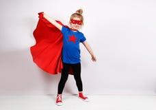 La fille blonde de six ans s'est habillée comme le super héros ayant l'amusement à la maison Mur blanc sur le fond Photographie stock