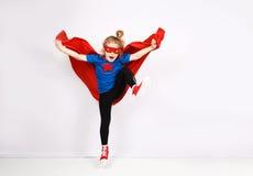 La fille blonde de six ans s'est habillée comme le super héros ayant l'amusement à la maison Mur blanc sur le fond Image stock