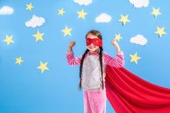 La fille blonde de six ans s'est habillée comme le super héros ayant l'amusement à la maison Badinez sur le fond du mur bleu lumi Image stock