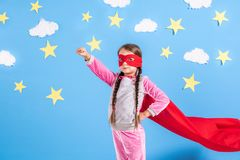 La fille blonde de six ans s'est habillée comme le super héros ayant l'amusement à la maison Badinez sur le fond du mur bleu lumi Images stock