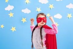 La fille blonde de six ans s'est habillée comme le super héros ayant l'amusement à la maison Badinez sur le fond du mur bleu lumi Photo stock