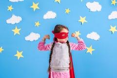 La fille blonde de six ans s'est habillée comme le super héros ayant l'amusement à la maison Badinez sur le fond du mur bleu lumi Image libre de droits