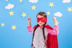 La fille blonde de six ans s'est habillée comme le super héros ayant l'amusement à la maison Badinez sur le fond du mur bleu lumi Photographie stock libre de droits