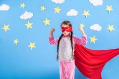 La fille blonde de six ans s'est habillée comme le super héros ayant l'amusement à la maison Badinez sur le fond du mur bleu lumi Photos libres de droits