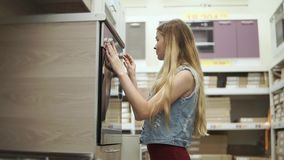 La fille blonde examine un cuiseur moderne avec le four dans une boutique banque de vidéos