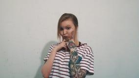 La fille blonde mignonne dans la chemise rayée avec des tatouages a mis des doigts sur les joues enflées banque de vidéos
