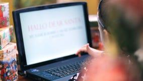 La fille blonde mignonne dans une belle robe imprime une lettre à Santa sur un ordinateur portable, près d'un arbre de Noël, déco banque de vidéos