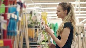 La fille blonde mince regarde sur un râteau de jardin dans un hall de supermarché clips vidéos