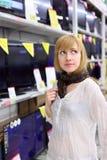 La fille blonde pense à acheter la TV dans le supermarché Image libre de droits