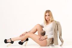 La fille blonde s'asseyent sur le plancher Image libre de droits