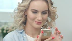 La fille blonde s'assied dans un salon et regarde le sourire d'écran de smartphone Photo libre de droits