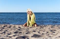 La fille blonde s'assied près de la mer sur ses genoux Image stock