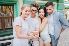 La fille blonde se tient avec ses amis et juge le téléphone disponible Tous regardent lui et le sourire Blond Image stock