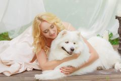 La fille blonde se trouve dehors avec un chien blanc dans des mains Photo stock