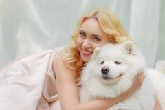 La fille blonde se trouve dehors avec un chien blanc dans des mains Images stock