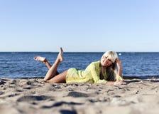 La fille blonde se trouve près de la mer sur ses genoux Photo libre de droits