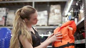 La fille blonde vérifie l'attache sur le gilet de sauvetage vif dans un magasin banque de vidéos