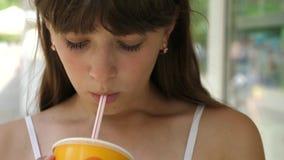 La fille boit du jus du tube dans la ville à la fenêtre de boutique dans l'après-midi et sourit Plan rapproché clips vidéos