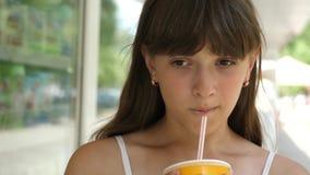 La fille boit du jus du tube dans la ville à la fenêtre de boutique dans l'après-midi et sourit Plan rapproché banque de vidéos