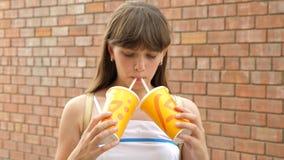 La fille boit du jus du tuyau dans la ville et sourit Plan rapproché banque de vidéos