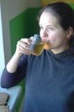 La fille boit du thé Photographie stock