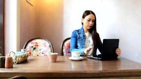 La fille boit du thé ou du café, et puis les préfère choisir un verre de vin clips vidéos