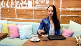 La fille boit du thé ou du café, et puis les préfère choisir un verre de vin banque de vidéos