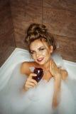 La fille boit du vin dans le bain avec la mousse images libres de droits