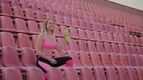 La fille boit l'eau apr?s la formation au stade clips vidéos