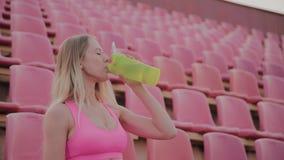 La fille boit l'eau apr?s la formation au stade banque de vidéos