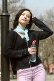 La fille boit l'eau et écouter la musique sur des écouteurs images stock