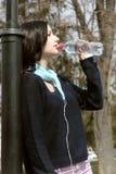 La fille boit l'eau et écouter la musique sur des écouteurs photo stock