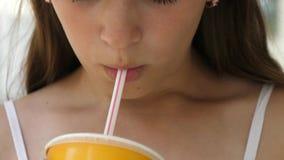 La fille boit le cocktail de la paille et les sourires marchent autour de la ville Plan rapproché clips vidéos