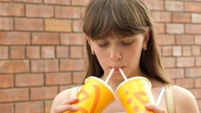 La fille boit le cocktail de la paille et les sourires marchent autour de la ville Plan rapproché banque de vidéos