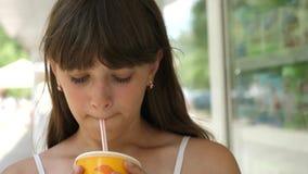 La fille boit le cocktail du tube dans la ville souriant et parlant Plan rapproché banque de vidéos