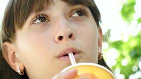 La fille boit le cocktail frais de la paille le jour chaud et rit en parc Plan rapproché banque de vidéos