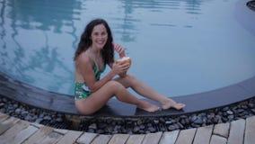 La fille boit le cocktail près de la piscine banque de vidéos