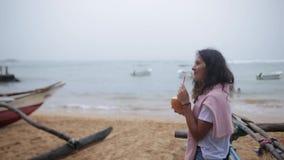 La fille boit le cocktail sur la plage banque de vidéos