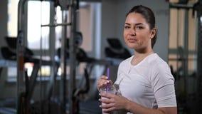 La fille boit la nutrition de sports dans le gymnase Boissons regardant la caméra et le sourire 4K MOIS lent clips vidéos
