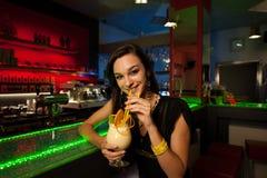 La fille boit un cocktail de colada de Pina dans la boîte de nuit Photographie stock libre de droits