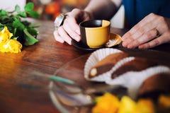 La fille boit une tasse noire et jaune de thé photos stock