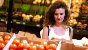 La fille bouclée choisit des tomates dans un supermarché banque de vidéos