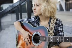 La fille bouclée fait la créativité, elle joue la guitare sur la rue images stock