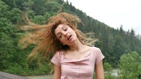 La fille bouclée heureuse dans les montagnes apprécie la pluie d'été sans parapluie La fille est heureuse et des rires gaiement banque de vidéos