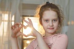 La fille bouclée a plié ses mains un en forme de coeur photos stock