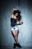 La fille bouclée se tient sur un mur texturisé, sa tête vers le bas Images stock