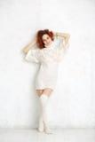 La fille bouclée rousse dans un blanc a tricoté le chandail et les bas stan Photographie stock libre de droits