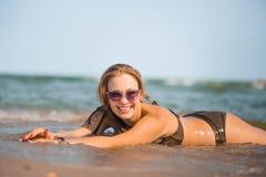 La fille bronzée sexy dans un maillot de bain se trouve sur le bord de la mer Photo stock